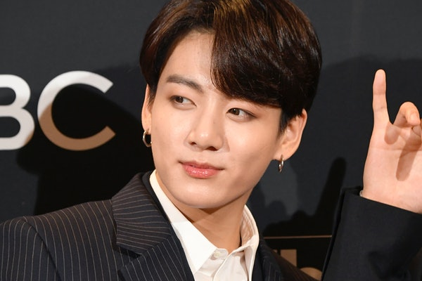 Jungkook from BTS rocking a shorter hairstyle while posing on a red carpet.