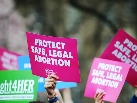 """A pro-abortion protester holds up a sign saying """"protect safe, legal abortion."""" A new California law will make public colleges offer medication abortions on campus."""