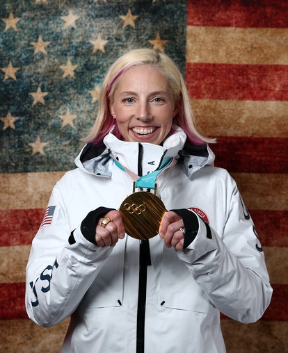 Kikkan Randall holds up her gold medal in front of an American flag. Randall was diagnosed with breast cancer and is now running the New York City marathon