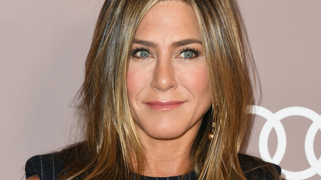 Jennifer Aniston hits the red carpet in a striped black dress.