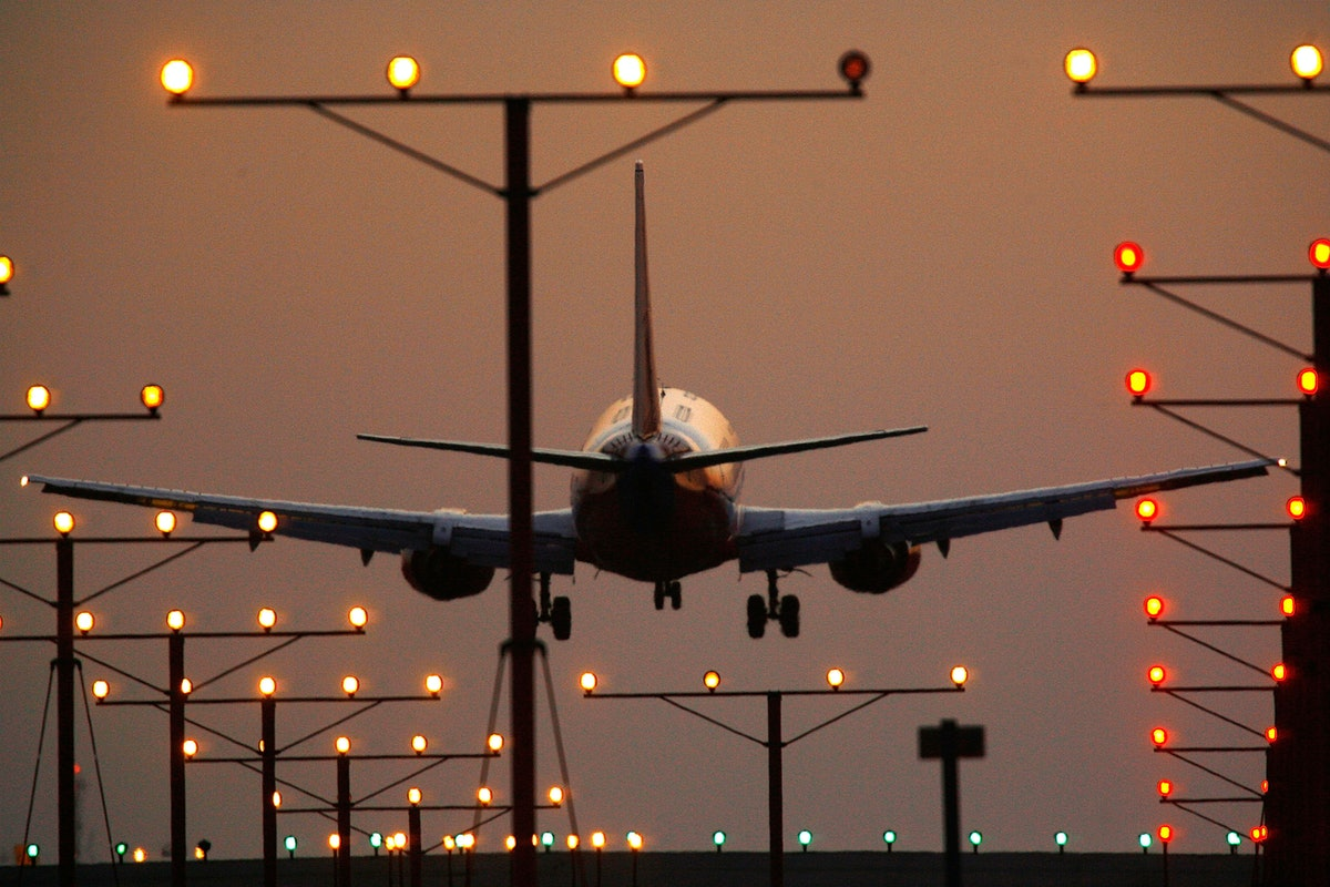 A plane taking off for a flight at twilight, with runway lights shining. The chances of a plane crash are extremely low.