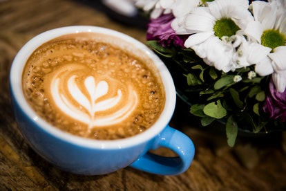 A latte in a blue mug. Bloating remedies can be as simple as swapping out milk for a non-dairy alternative