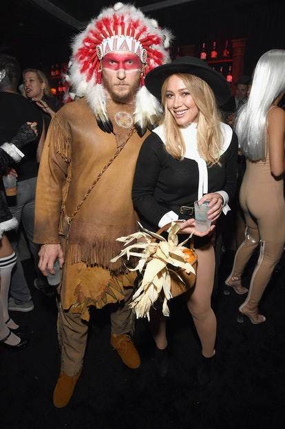 Hilary Duff and Jason Walsh wearing costumes of Native American clothing and a pilgrim outfit. Avoid...