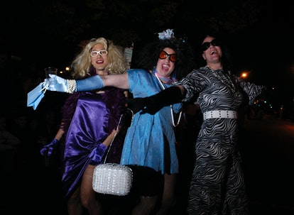 Three people pose with big smiles and their arms spread wide, dressed in femmey Halloween finery. Being trans on Halloween often means being able to express yourself in ways you might feel like you can't throughout the rest of the year.