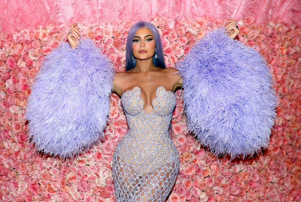 Kylie Jenner poses in front of a rose wall at the 2019 Met Gala in a purple dress with fluffy purple sleeves, and purple hair.