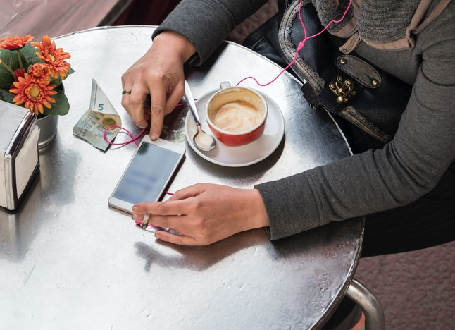 A person smokes while drinking a latte at an outdoor cafe. Social smoking is not any safer than smoking-smoking.