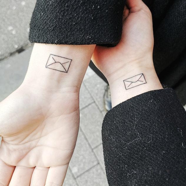 matching envelope tattoos on two wrists