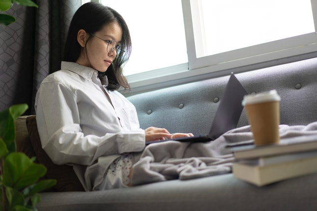 A person answers emails on a laptop from their couch at home. Answering emails after work hours can have numerous health effects.