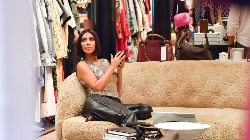Kim Kardashian sits on a fluffy tan couch in a store with her phone in her hand.