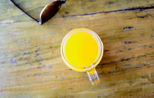 A glass of orange juice on a wood table. Orange juice is a healthy drink.