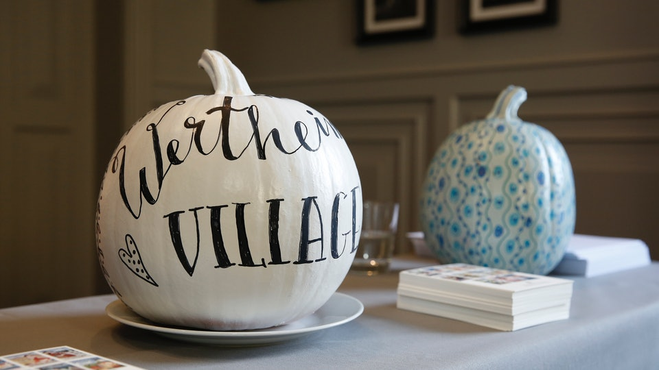 Two DIY stenciled pumpkins on a table