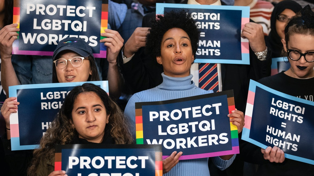 "People holding LGBTQ rights signs ahead of Supreme Court hearing which say ""protect LGBTQI workers."""