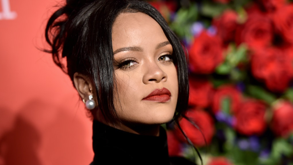 Rihanna in profile looks at the camera