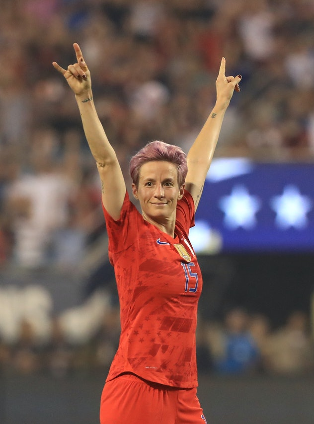 Megan Rapinoe celebrates with 2 hands in the air. Her quotes on equal pay are perfect for International Day Of The Girl.