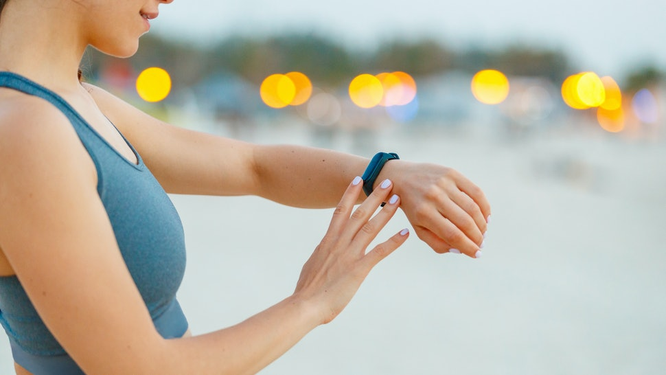 A woman reads her smartwatch for information from her period-tracking app.