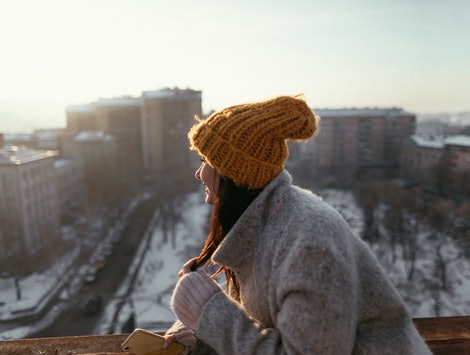 A woman in a hat looks out over a snowy cityscape. The winter solstice means that the days will soon get lighter.