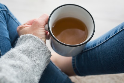 A woman sits crossed legged, holding a cup of coffee. Feeling depressed can be a sign your metabolis...