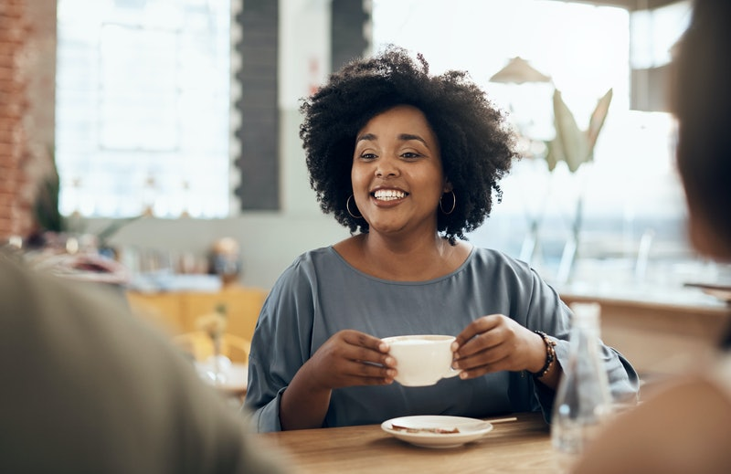 A woman drinks a cup of coffee. Cutting back to one cup of coffee a day may affect many aspects of your health, including the gut and digestion.