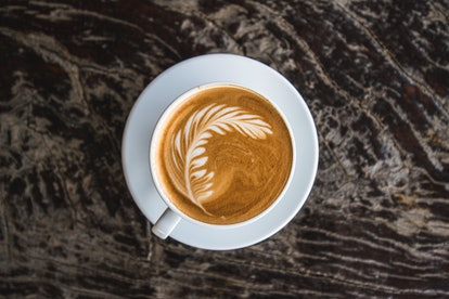 A cup of coffee sits on a counter. Reducing coffee intake can induce symptoms of withdrawal, like headaches, moodiness and difficulty concentrating.