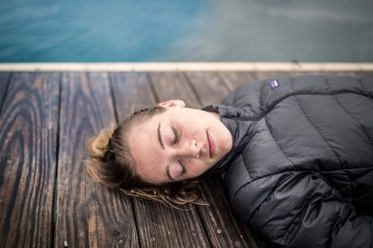 A woman sleeps on a pier. Reducing coffee consumption may help sleep patterns and improve restful sleep.
