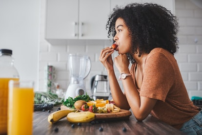 A woman eats a fruit platter. Flexitarianism may increase fiber intake and help with gut health.