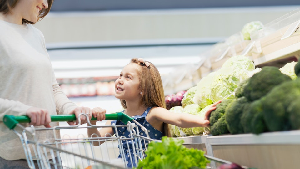woman and daughter push shopping cart in supermarket