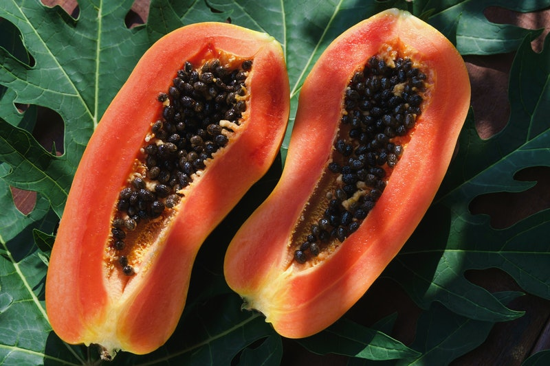 """Two papaya halves show their seedy interiors. If you're wondering """"is my vagina normal,"""" rest assured there's a 10/10 chance it is."""