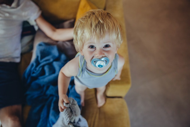 A small child looks up at the camera with a light blue pacifier in their mouth. Hiccups activate brain waves that help infants and babies learn how to voluntarily control their breath, but they may not have any benefits in adulthood.