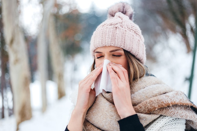 A woman blows her nose in a wintry landscape. Fluctuating hormones throughout the menstrual cycle can change your respiratory cycle function.