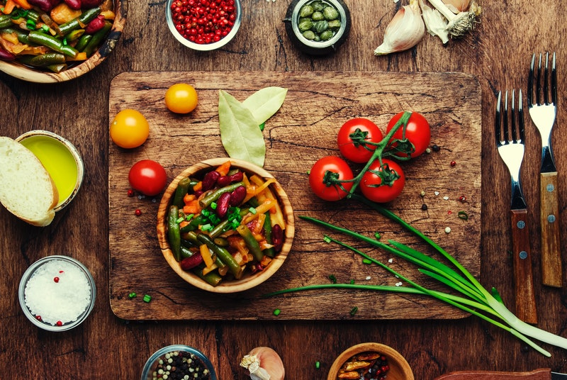 An array of vegan dishes and veggie ingredients lay on a wooden table and cutting board. Vegan Thank...