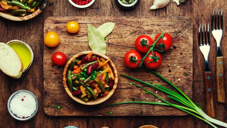An array of vegan dishes and veggie ingredients lay on a wooden table and cutting board. Vegan Thanksgiving entrees and main dishes are both fun to make and delightful to eat.