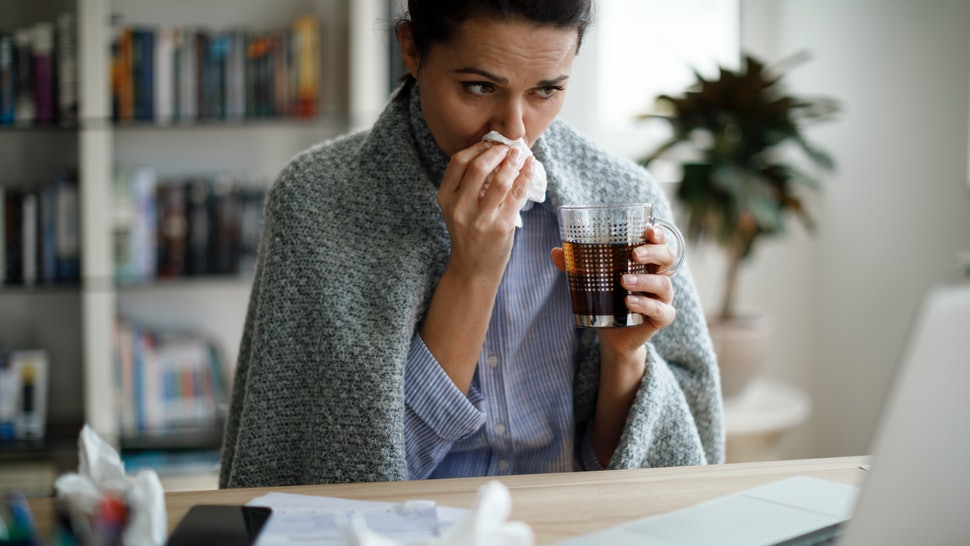 A woman fights the flu. Serious influenza infections can influence the menstrual cycle, but only in some people, experts say.