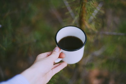 An enamel mug with black tea. Caffeine, whether we have it in tea or coffee, can be helpful for health in low doses in the long term.