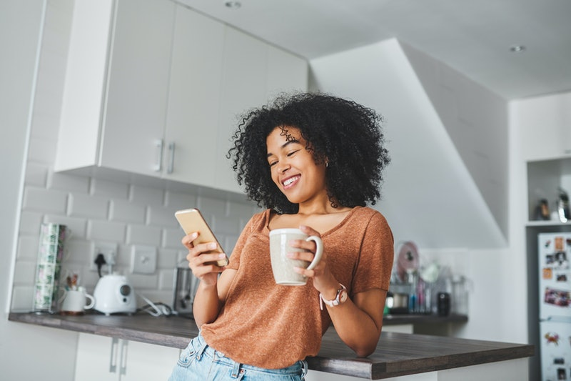A woman drinks tea in her kitchen. Switching from coffee to tea can have surprising effects on your body.
