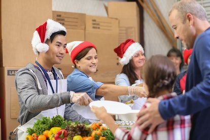 Some volunteers at a local food bank get in the holiday spirit by wearing Santa hats.