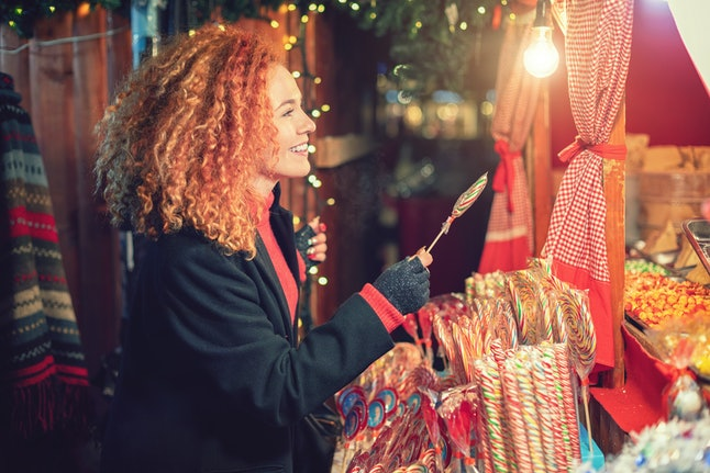 A woman shops at a Christmas market. Shopping for deals can create a positive emotional response.