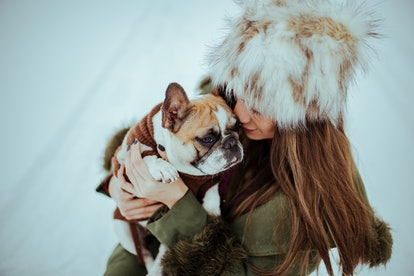 A woman hugs her dog in the snow. Scientists disagree about how cooler temperatures might affect brain performance in men and women.
