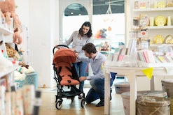 a pregnant woman and her partner shopping for strollers