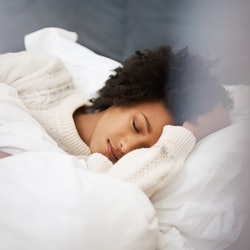 A person sleeping in bed in a white sweater, and under a white comforter. It can be tricky to tell if you're experiencing sleep terrors when you live alone, but experts say there are signs to look for.
