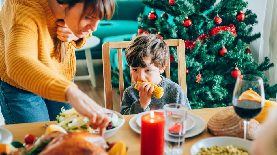 a family eating Thanksgiving dinner with a Christmas tree in the background