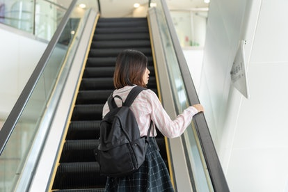 A woman rides an escalator in an airport. Hand rails, elevator buttons and other communal surfaces can carry flu germs in winter.
