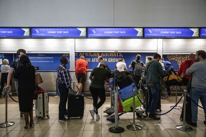 People wait in line at an airport. Flu germs can transmit easily in crowded spaces in airports.