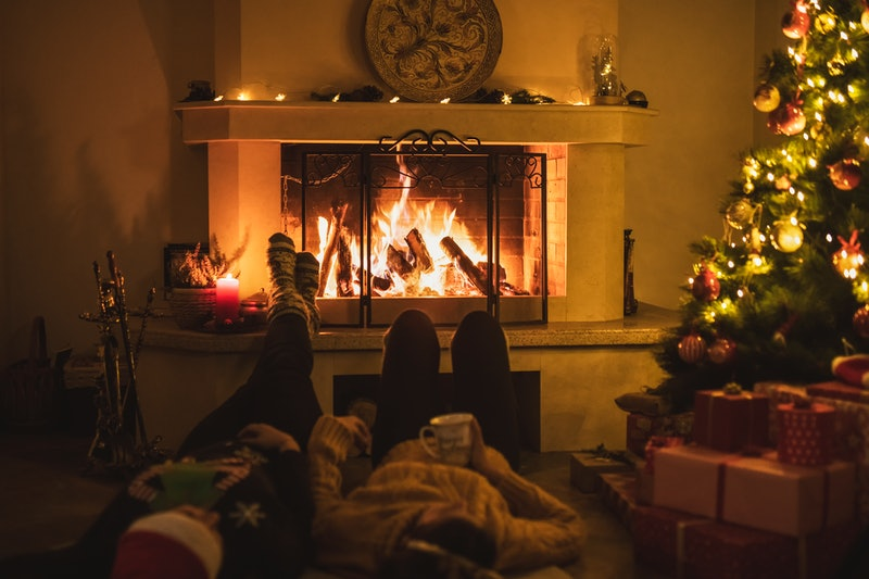 Two siblings talk in front of the fireplace during the holidays. If you're not out or newly out during the holidays, an expert suggests coping tips