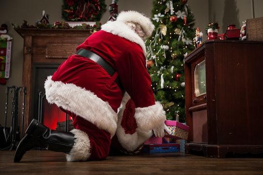 santa leaving presents under the tree