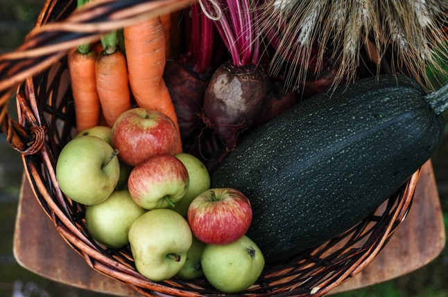 An assortment of fresh fruits and vegetavles arranged in a wooden basket. Cooking your own Thanksgiving main to bring to your family's gathering might help ease social tensions, and your own hunger.
