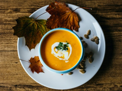 A bowl of fall-themed soup surrounded by leaves on the bottom plate. Setting boundaries with your family when they try to bait you about your veganism is important.