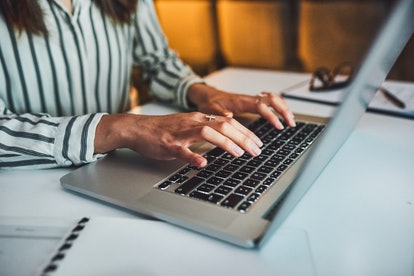 A person is typing on their computer at their desk at work. Rebecca says that asking for accommodations at work left her feeling empowered.