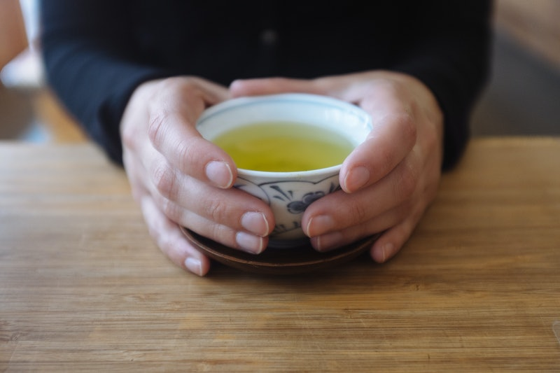 A pair of hands around a cup of green tea. Green tea comes in many varieties, and switching to green...