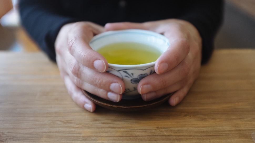 A pair of hands around a cup of green tea. Green tea comes in many varieties, and switching to green tea can have health benefits.