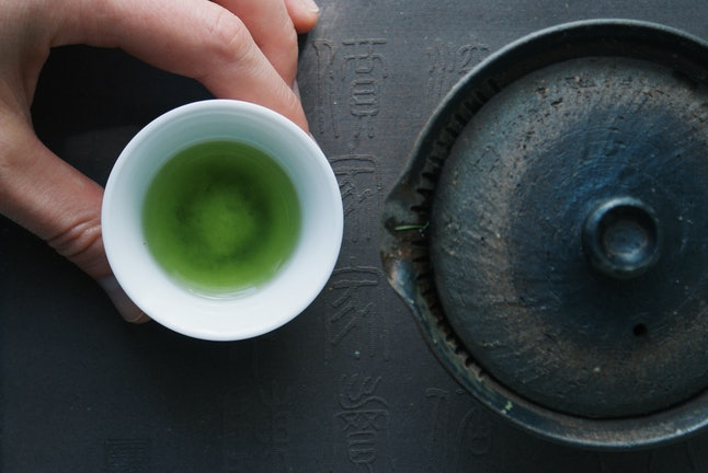 Green tea in a ceramic bowl beside a teapot. Swapping green tea for morning coffee may improve the bacterial balance in your mouth, helping oral health.